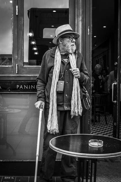 Old man with beard , walking stick, hat, scalf and camera round his neck standing outside coffee shop, Western Road Brighton UK. Street Photography. Monochrome Portrait.  © P. Maton 2015 eyeteeth.net