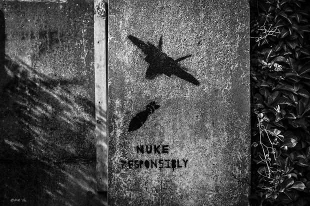 Concrete wall with stencil street art of aeroplane dropping a bomb with the words 'Nuke Responsibly'  written below. Abstract Urban Street Photography. North Place Brighton UK. Monochrome Landscape. © P. Maton 2015 eyeteeth.net
