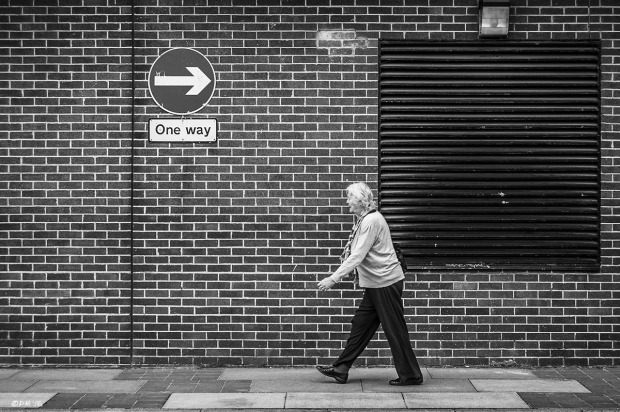 Mature woman walking in front of brick wall in opposite direction to an arrow sign saying one way. Waitress Car Park, Lewes East Sussex UK. Street Photography. Monochrome Landscape. © P. Maton 2015 eyeteeth.net