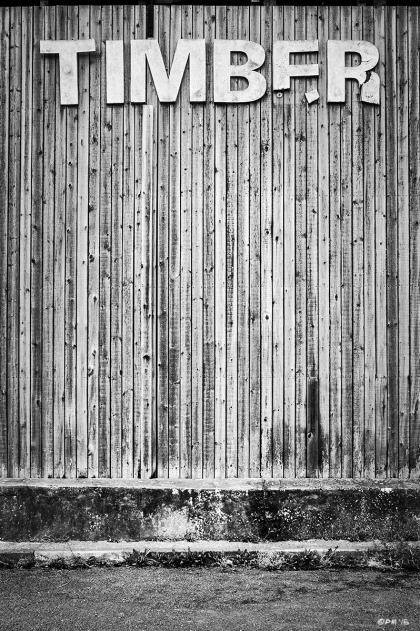 Wood plank wall with dilapidated sign saying Timber, Timber Merchants wall, Lewes East Sussex UK. Monochrome Portrait. © P. Maton 2015 eyeteeth.net