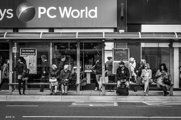 Two old women sisters sitting among people at bus stop in front of PC World, opposite Churchill Square, Western Road  Brighton UK. Monochrome Landscape. © P. Maton 2015 eyeteeth.net