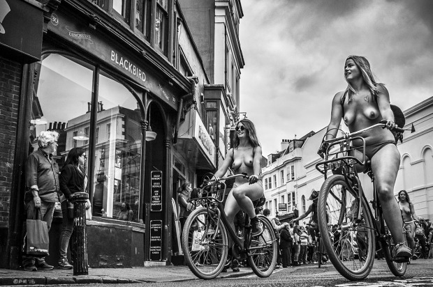 Two smiling topless women riding bicycles along street with people looking on, Naked Bike Ride 2015,  Ship Street Brighton UK. Monochrome Landscape. © P. Maton 2015 eyeteeth.net