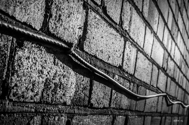 Cable fixed to brick wall with highlight from sun. Hove East Sussex. Monochrome Landscape. © P. Maton 2015 eyeteeth.net