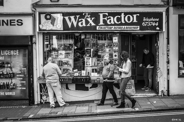 Wax Factor Record and Book store with Man browsing Trafalgar Street Brighton UK. Monochrome Landscape. © P. Maton 2015 eyeteeth.netstock on street as people walk by and shop keeper examining vinyl record in doorway.