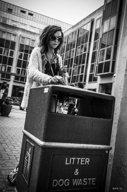 Woman stubbing out cigarette on  public waste bin, Bartholomew Square Brighton Sussex UK . Urban Street scene. Monochrome Portrait. © P. Maton  2015 eyeteeth.net
