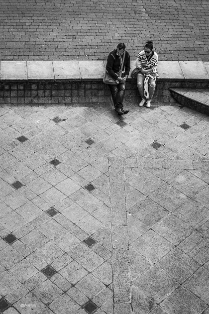 Man and woman couple sitting on wall between pathway and paved area seen from above. King's Road Arches Brighton UK. Monochrome Portrait. © P. Maton 2015 eyeteeth.net