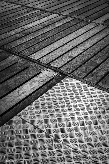 Worn wooden boards and metal tread floor plate. Palace Pier Brighton UK. Abstract Monochrome Portrait. © P. Maton 2015 eyeteeth.net