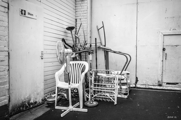 Free standing Fan, chair, folding bed and other household furniture in corner of yard by toilet door with Men sign. London Road, Bexhill on Sea, East sussex UK.  Monochrome Landscape. © P. Maton 2015 eyeteeth.net