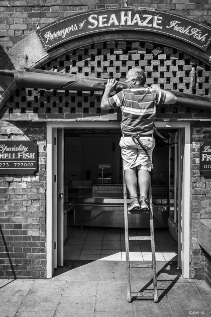 Man up ladder taking down awning in front of fish shop entrance , Sea Haze King's Road Arches Brighton UK. Monochrome Portrait. © P. Maton eyeteeth.net