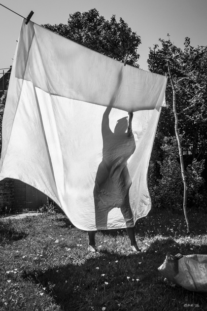 Bed sheet on washing line with silhouetted figure of a woman reaching upward. Hove UK. Urban Monochrome Portrait. © P. Maton eyeteeth.net