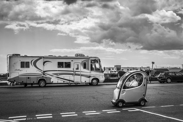 Mobility scooter / buggy driving along road in front of mobile home on Hove sea front. Kingsway Hove UK. Monochrome Landscape. © P. Maton 2015 eyeteeth.net