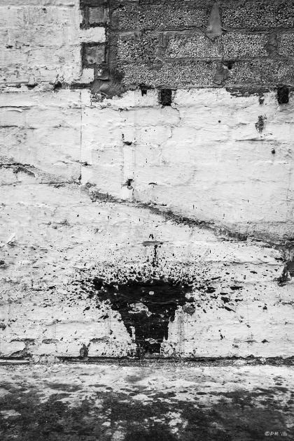 Black paint splash resembling female pubic hair on rough white wall with exposed concert blocks. London Road, Bexhill on Sea, East sussex UK. Monochrome Portrait. © P. Maton 2015 eyeteeth.net