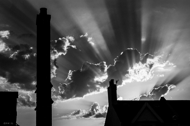 Sunbeams through clouds at sunset with silhouetted roofs and chimneys in foreground.  Scott Road, Hove UK. Monochrome Landscape. © P. Maton 2015 eyeteeth.net