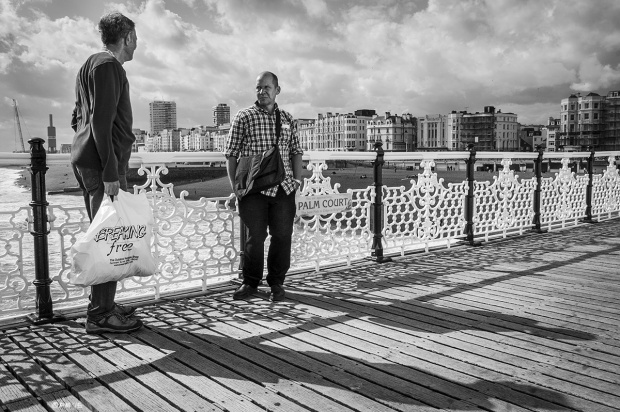 Two men facing each other by railings on Pace Pier Brighton UK, view of seafront and building of i360 tower in background. Monochrome Landscape. © P. Maton 2015 eyeteeth.net