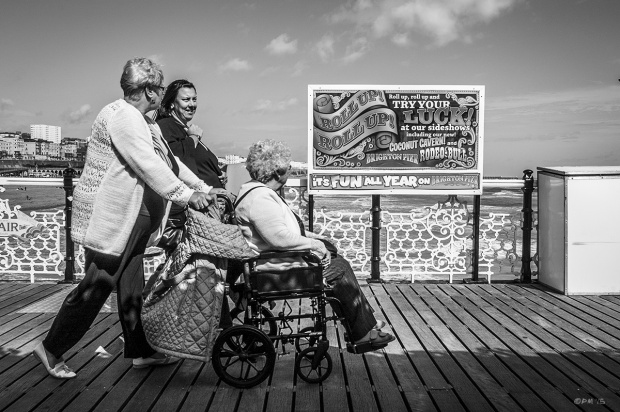 Two women pushing a third in a wheelchair in fromt of a sign saying 'Roll Up, Roll Up' on Palace pier Brighton UK. Monochrome Landscape. © P. Maton 2015 eyeteeth.net