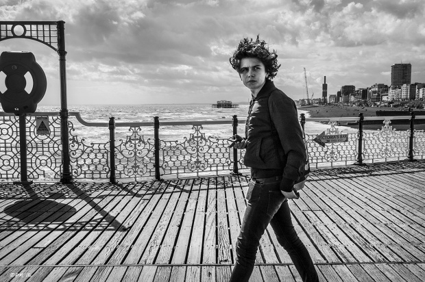 Young man looking passed viewer, walling along brighton pier with hair blowing in the wind . View of sea front and West Pier in background. Palace Pier Brighton UK. Monochrome Landscape. © P. Maton 2015 eyeteeth.net