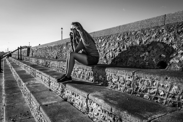 Woman in shorts sitting on sea wall steps looking away into sunlight vanishing point. Hove seafront Sussex UK. Monochrome landscape. © P. Maton 2015 eyeteeth.net