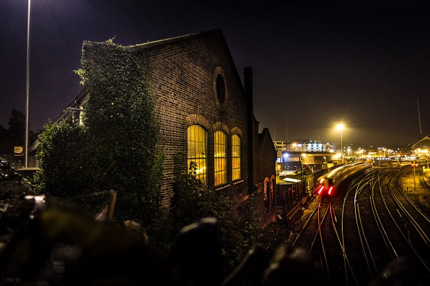 Victorian railway building at night with train passing and lights reflected in windows. Brighton Train Care Depot, Combined Engeneering Depot. Brighton Sussex UK. Urban Colour Landscape. © P. Maton eyeteeth.net
