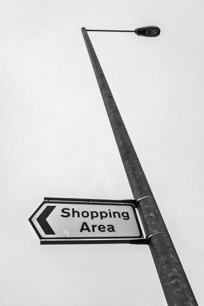 Lamp post with shopping area sign pointing left. against formless cloudy sky. Hove UK. Minimal Abstract Street Urban. Monochrome Portrait. © P. Maton 2015 eyeteeth.net