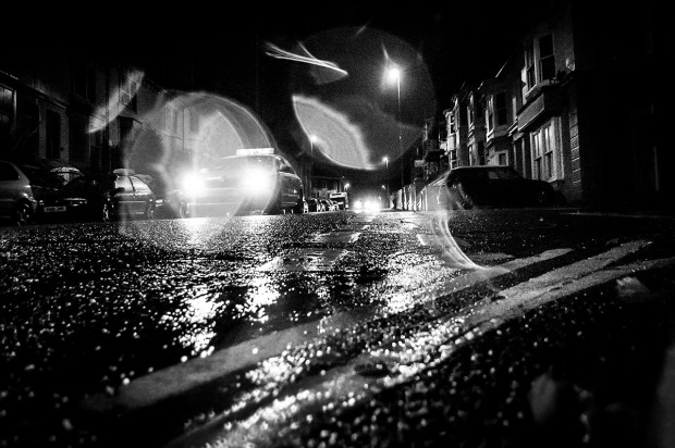 Taxi in the rain at night with water drops on lens shot from low angle. Chatham Place Brighton UK. Monochrome Landscape. © P. Maton 2015 eyeteeth.net