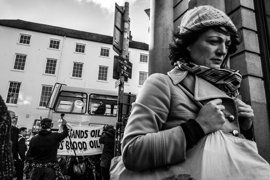 Woman walking away from HSBC protest on Bond Street Brighton UK, Banner with the words Tar Sands Oil Is Blood Oil in background. Street Photography Monochrome. © P. Maton 2015 eyeteeth.net