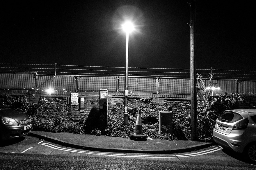 Street Lamp number two by parking ticket machine and telegraph pole against fenced wall by railway escarpment on Howard Place Brighton UK. Monochrome Landscape. P. Maton 2015 eyeteeth.net