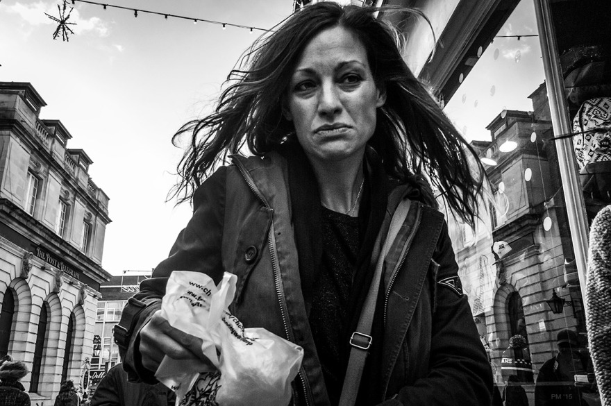 Woman with upset expression walking in street with hair blowing in wind. Bond Street Brighton UK. Street photography. Monochrome Landscape. © P. Maton 2015 eyeteeth.net