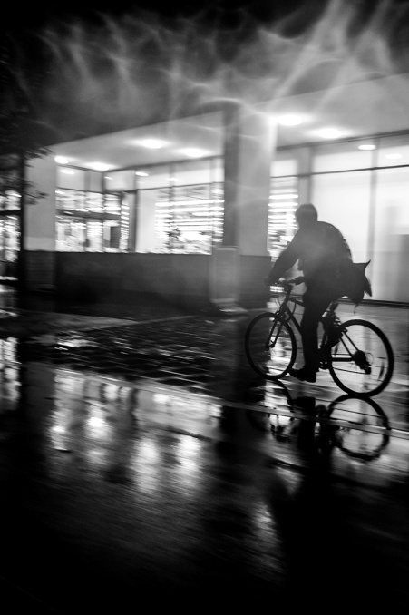 Silhouette of man cycling at night in front of supermarket with flare from lights and water drops on lens. New England Street Brighton UK Monochrome Portrait. © P. Maton 2015 eyeteeth.net Dramatic haunting nighttime urban street photography