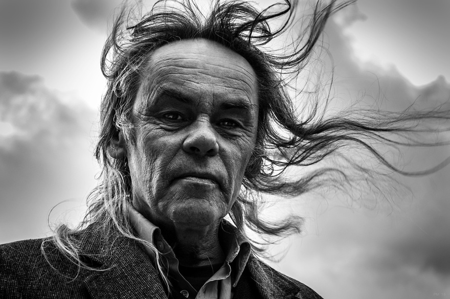 Man with rugged aged face and long hair blowing in wind. Black and white portrait. Oxfordshire, England UK. © P. Maton 26/12/15