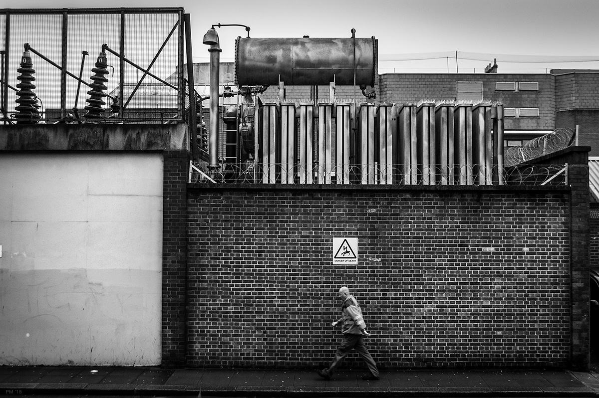 Man walking by brick wall with electrical substation above. Grim, bleak black and white British industrial urban street scene. Brighton UK © P. Maton 2015 eyeteeth.net