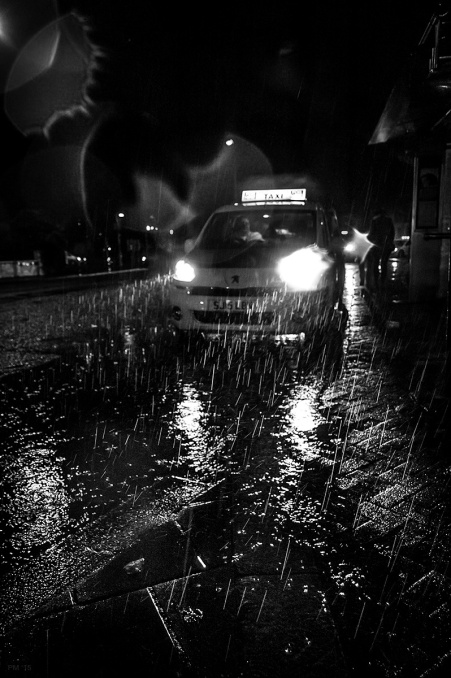 Taxi waiting in rain at night with raindrops caught in light beams. Saint Peter's Place Brighton UK. Urban street night photography monochrome place and white portrait © P. Maton 2015 eyeteeth.net