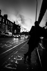 Silhouette of man leaning against bus stop shelter next to road with cars illuminating street and dawn light over Preston Circus, Brighton UK. Monochrome black and white urban street photography. © P. Maton 2016 eyeteeth.net