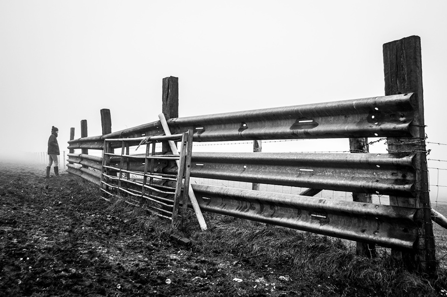 Farm armco fence by gate with woman standing in distance on foggy day. Fire Beacon, South Downs, Seven Sisters Country Park. East Sussex UK. Black and white landscape. © P. Maton 2016 eyeteeth.net