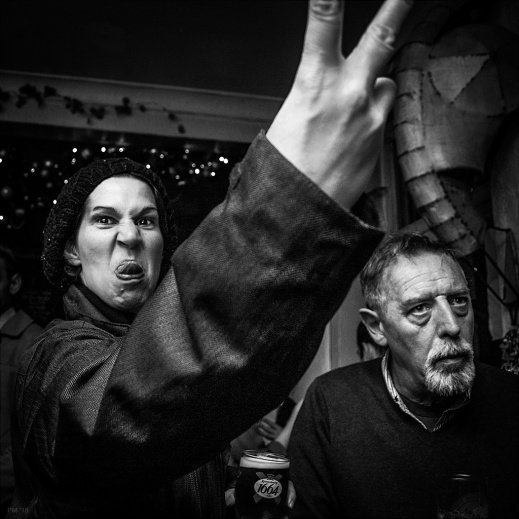 Woman in English pub pulling a face and sticking two fingers up at the camera while holding a pint of larger. Britain nightlife drinking culture. Shakespeare's Head pub Brighton. Black and white documentary photography. © P. Maton 2015 eyeteeth.net