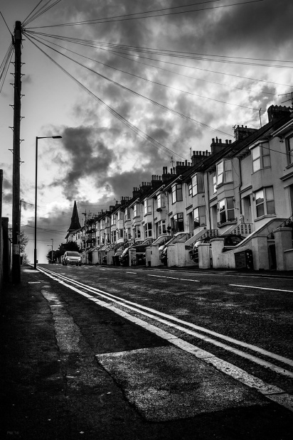 View up wet road next to terrace of houses with car approaching and telegraph pole against scattered cloudy sky. Black and white urban street scene. © P. Maton 2015 eyeteeth.net