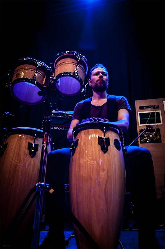 Conga bongo player for J-Felix on stage at Brighton Dome. Dramatic angle with blue back lighting. Brighton Music colour photograph. ©P. Maton 2016 eyeteeth.net