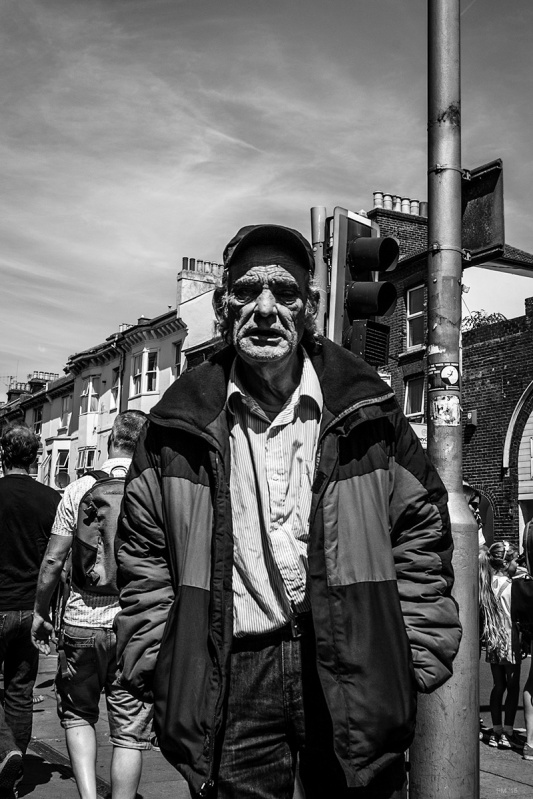 Old man with weathered face by lamp post in sunshine on London Road, Brighton UK. Black and white street photography. © P. Maton 2015 eyeteeth.net