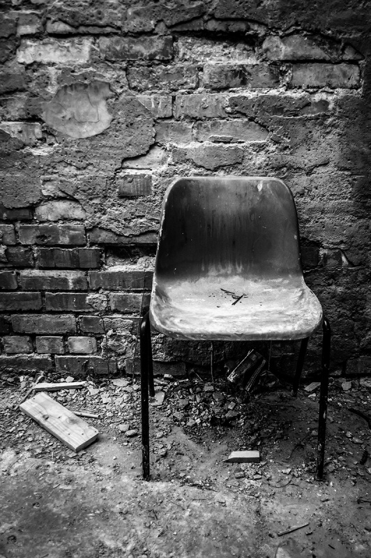 Dirty dusty plastic chair in front of crumbling plaster and brick wall with detritus on floor. Abandoned urban spaces photograph. Bexhill East Susex UK. © P. Maton 2016 eyeteeth.net