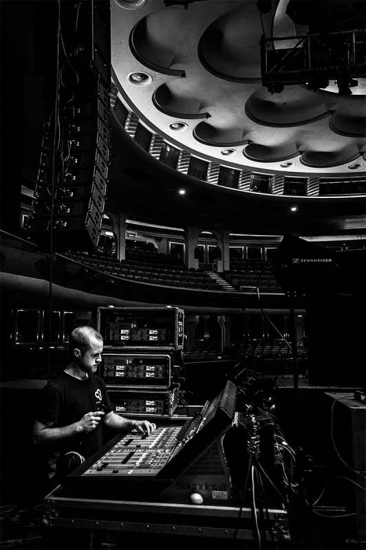 Sound engineer standing at mixing desk with theatre circle in background and illuminated ceiling. Brighton Dome UK. Black and white photograph. ©P. Maton eyeteeth.net
