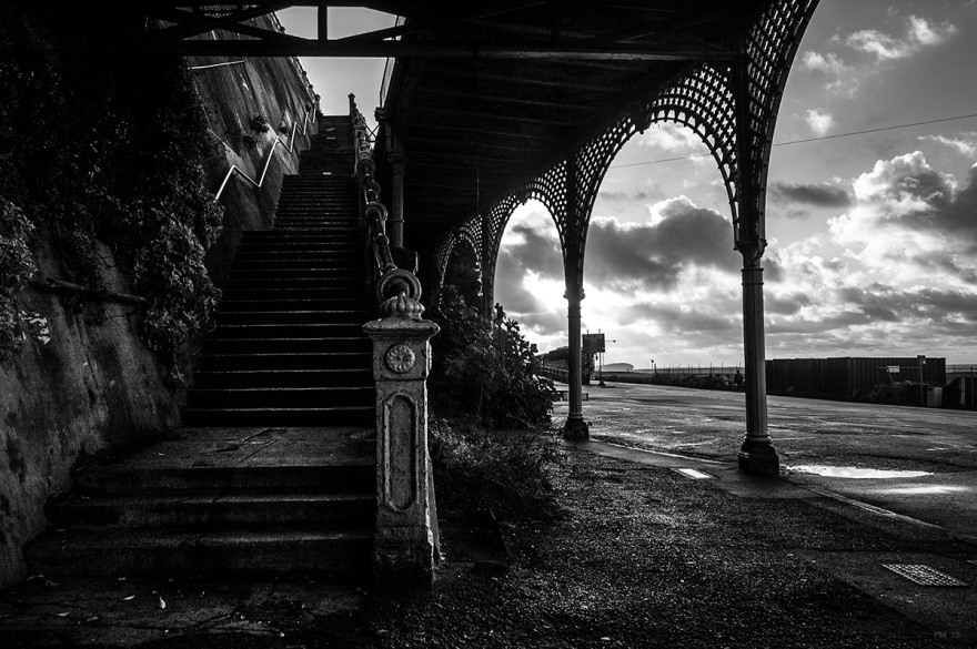 Staircase leading from Madeira Drive up to Marine Parade on Brighton seafront, victorian Regency iron arches and morning sun bursting through clouds. Brighton UK Gritty urban landscape. Black and white photograph © P. Maton 2014 eyeteeth.net