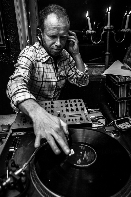 Man DJ listening to headphones reaching over mixer and record deck . Shakespeare's Head pub Brighton Sussex UK. Black and white nightlife photograph. © P. Maton 2016 eyeteeth.net