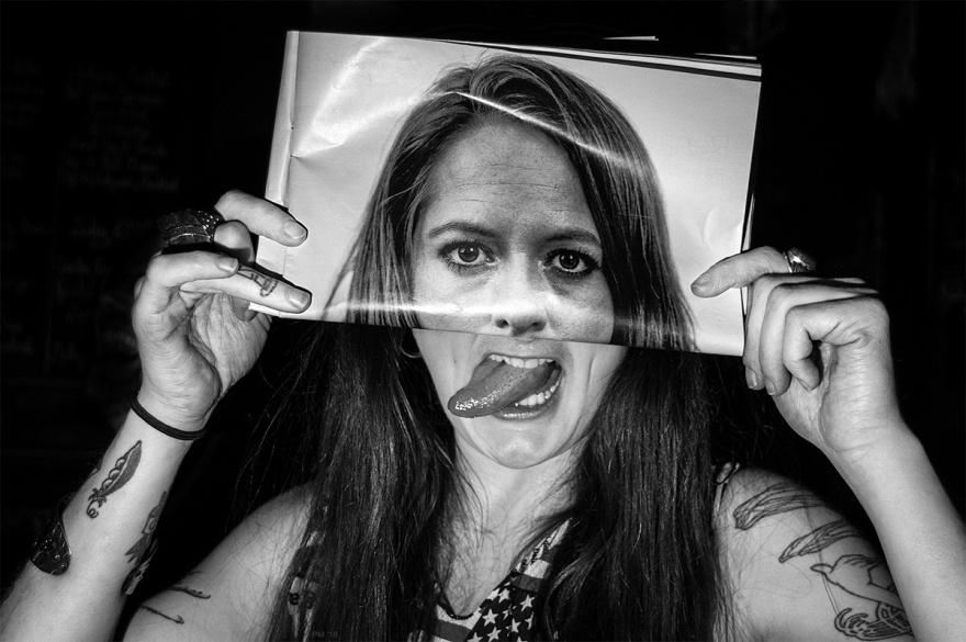 woman with tongue sticking out holding magazine photo over her face. Brighton, Sussex UK nightlife photograph. © P. Maton 2016 eyeteeth.net