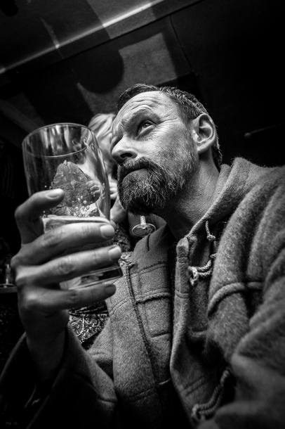 Man with a beard in duffel coat holding a pint of beer. The Shakespeare's Head Pub, Brighton UK. Black and white nightlife photography. © P. Maton 2016 eyeteeth.net