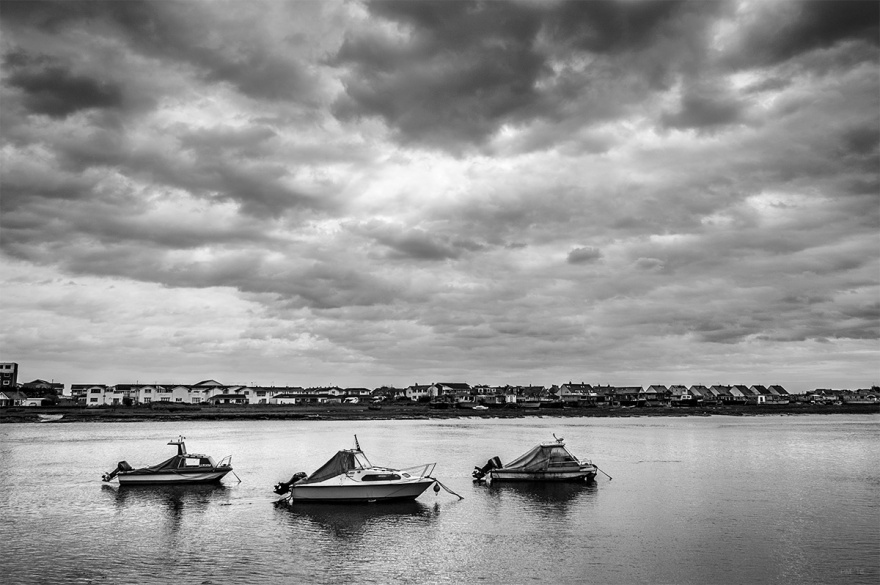 Three boats / motor launches anchored on the River Adur at Shoreham, West Sussex. Dramatic overcast cloudy sky, calm water with houses in distance. Black and white maritime nautical scene. Moody and romantic documentary photograph. © P. Maton 2016 eyeteeth.net