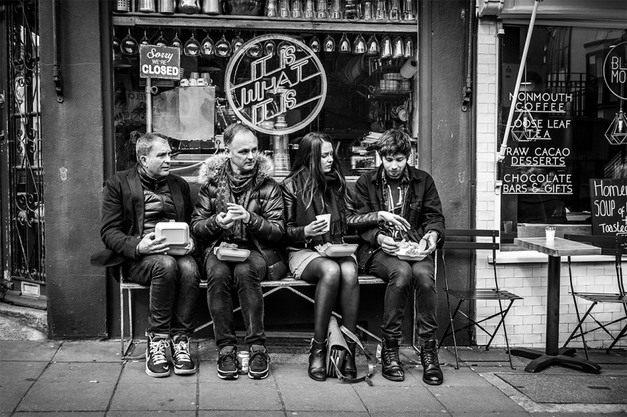 Black and white street scene with woman and three men sitting eating chips from boxes. Gloucester Road North Laine Brighton UK. Urban street photography. © P. Maton 2016 eyeteeth.net