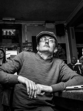 Man in flat cap with glasses sitting staring upwards. Shakespeare's Heat Pub Brighton UK. Black and white nightlife photography. © P. Maton 2016 eyeteeth.net