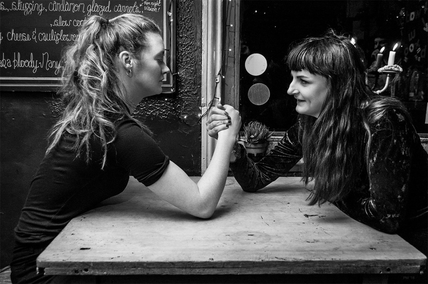 Two women arm wrestling in a bar. Brighton UK. Nightlife photography black and white. © P. Maton 2016 eyeteeth.net