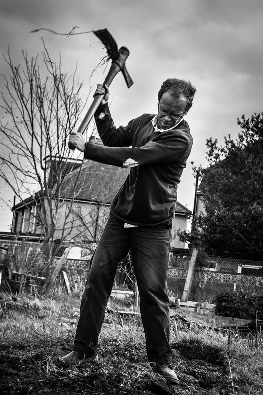Man tilling soil with a Mattock on Southwark allotment West Sussex UK. Rural Urban Black and white photography. © P. Maton 2016