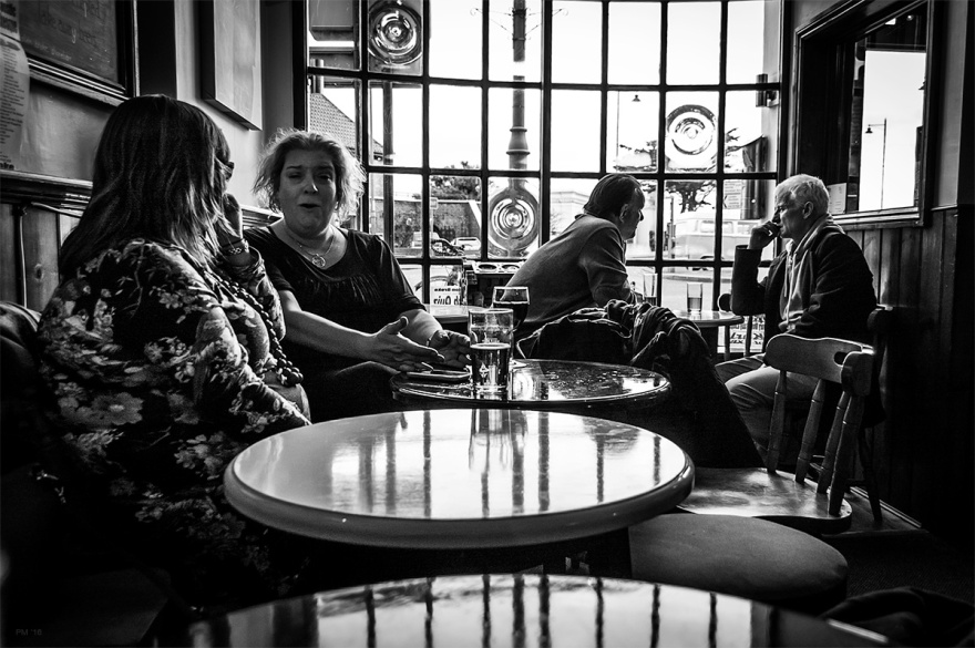 Two women talking at table in a bar with two men by window in background. The Piston Broke pub Shoreham by Sea, West Sussex UK. Black and white urban street photography. © P. Maton 2016 eyeteeth.net