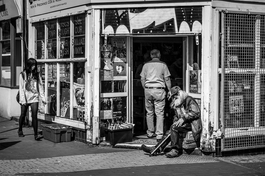Old man sitting outside Across the Tracks record shop on Sydney Street Brighton UK. black and white urban street photography. ©P. Maton 2016 eyeteeth.net